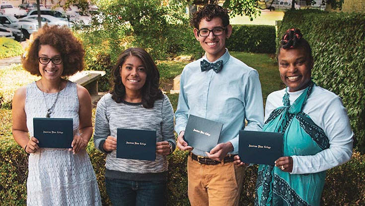 Four students holding their scholarship awards and smiling